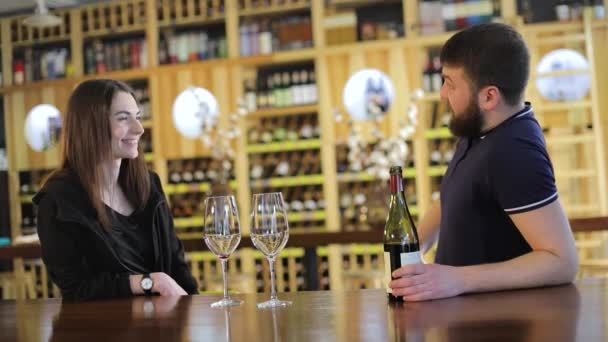 Egy lány és egy srác egy étteremben kommunikálni, és vörös bort inni, egy fiatal pár ital vörösbor egy asztalnál egy étteremben, vagy kávézóban
