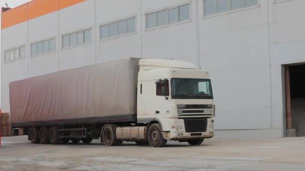 Die Bewegung eines weißen Lastwagens auf der Straße, weißer Sattelzug fährt durch die Fabrik