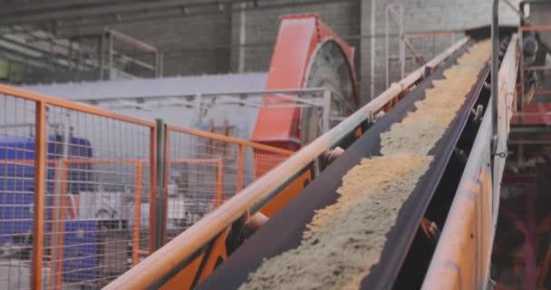 Dopravníkový pás s pískem a kovovými kuličkami. Dopravníkové pásy v továrně