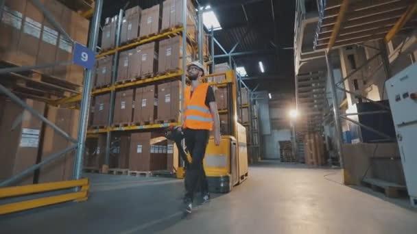 Egy munkás sétál át a raktáron egy elektromos hidraulikus targoncával. Egy munkás rakományt szállít a raktáron keresztül.