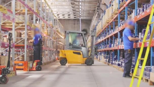 Villástargonca egy nagy raktárban. Az emberek egy raktárban dolgoznak. Ipari belső tér