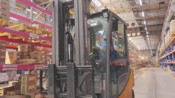 Ve skladišti jezdí vysokozdvižný vozík. Vysokozdvižný vozík ve velkém průmyslovém skladu