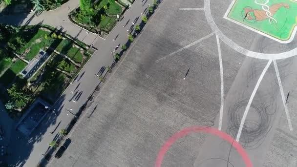Žena stojí sama ve velkém prostoru, nikdo kolem není zastřelen ze vzduchu. Osamělá žena stojí na náměstí pohled shora