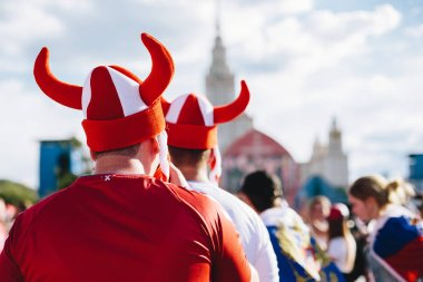 MOSCOW, RUSSIA - JUNE 2018 Danish fans wearing Viking hats painted in the colors of the national flag of the fan zone during the World Cup