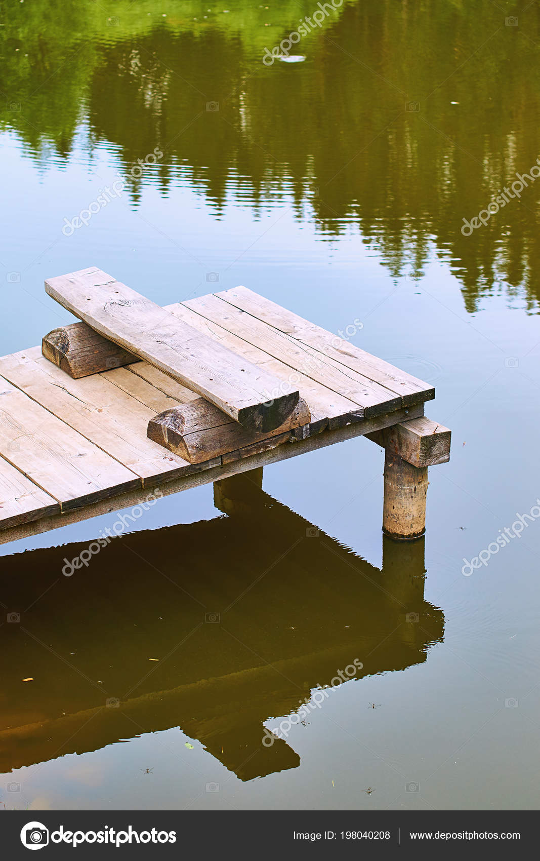 Cozy fishing bench on a wooden pier at the shore of a calm
