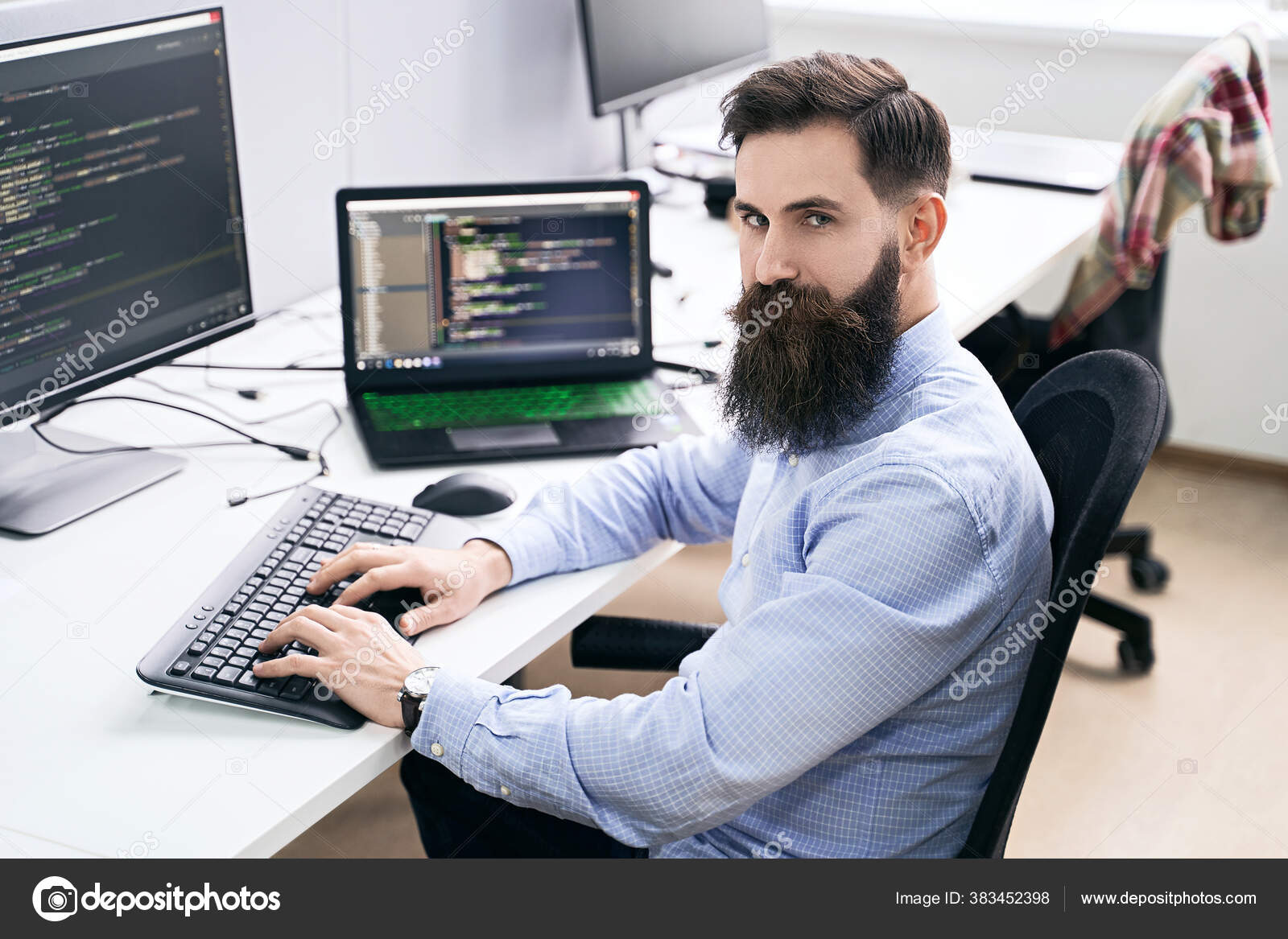 Serious computer programmer developer working in IT office, sitting at desk and coding, working on a project in software development company or startup. High quality image. Stock Photo by ©oleksandrberezko 383452398