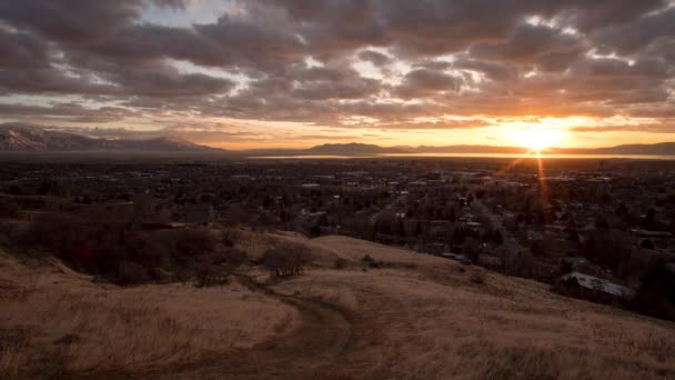 Sunset time lapse from mountain side with dirt road in foreground displaying magnificent colors