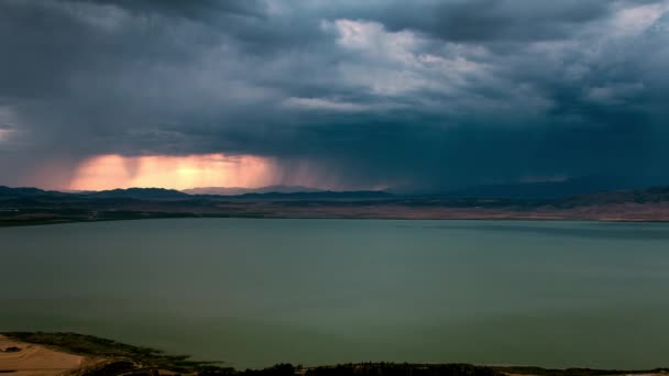 Dark storm clouds rolling over the landscape during colorful sunset as it blocks out the sky over Utah Lake.