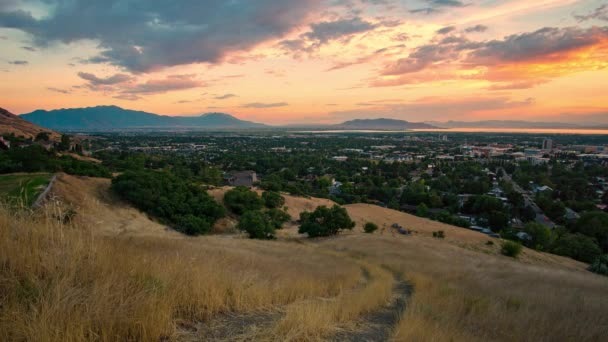 Colorful sunset overlooking Provo from grassy hill looking south across Utah Valley.