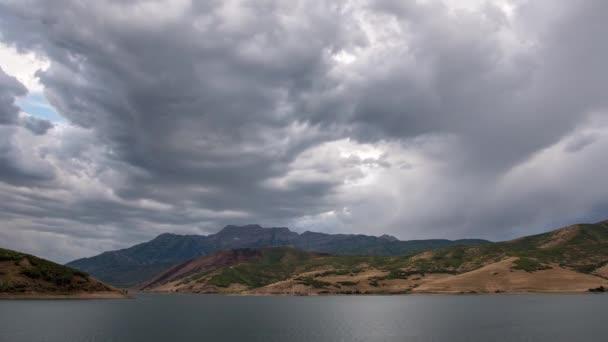 Časová prodleva temné mraky táhnou nad jezerem zobrazení pohoří při západu slunce.