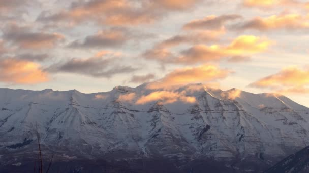 Clouds passing by mountain peak during sunrise