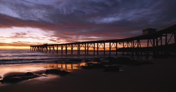 Pier silueta během barevného východu slunce na Catherine Hill Bay, jak vlny valí na písečné pláži v Austrálii.