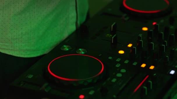 DJ controls the music console in a nightclub.