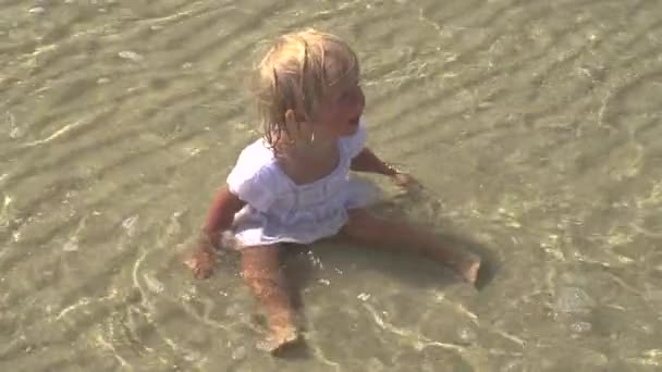 das Kind sitzt im Meer. kleines Mädchen sitzt im Wasser am Strand.