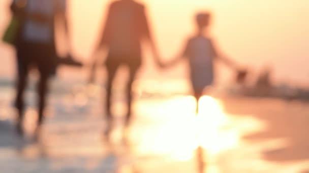 The family strolls along the seashore at sunset. Happy family on vacation.