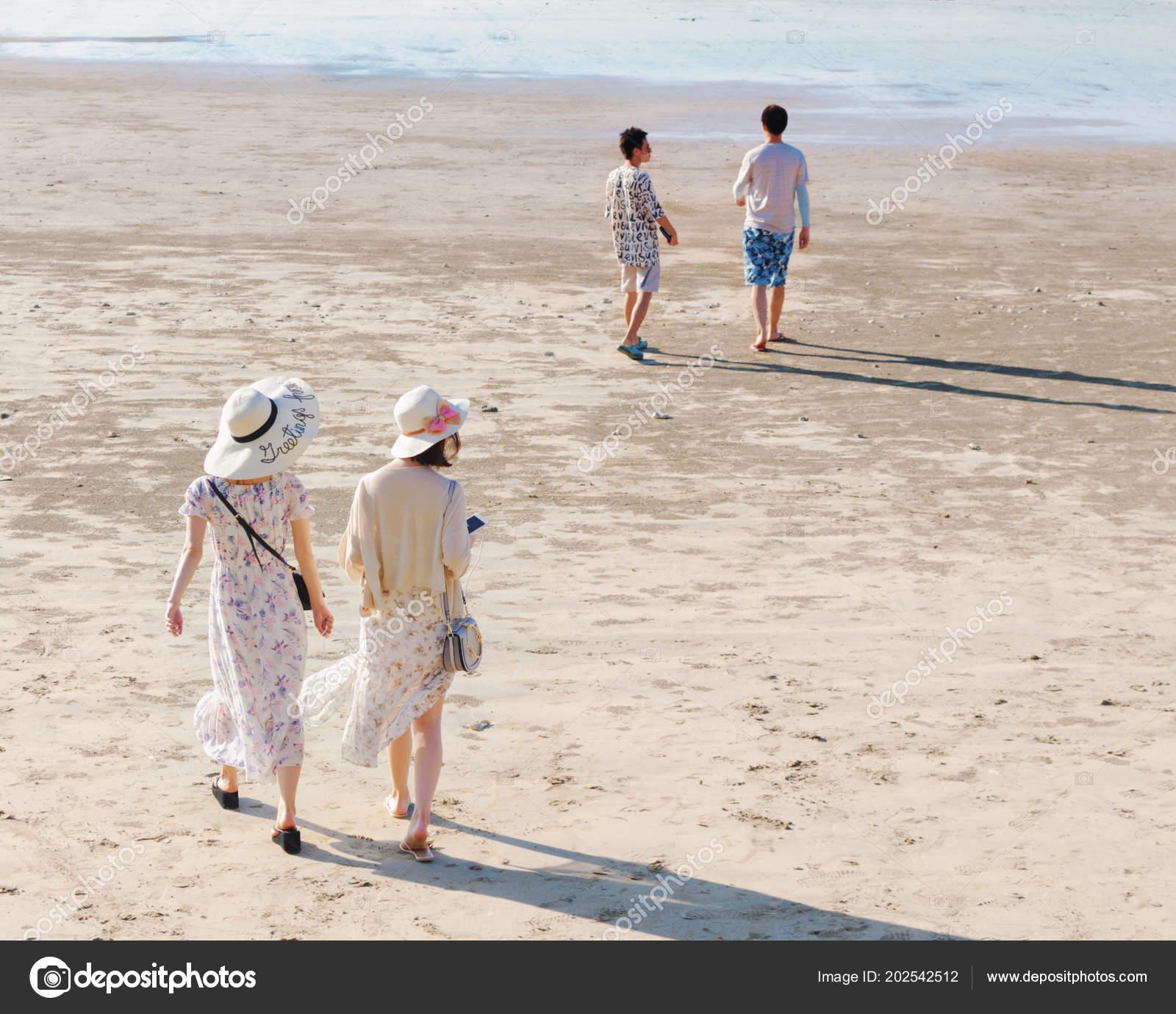 ff13ae9d892 ... ΠΙΣΩ ΟΨΗ των δύο νεαρών γυναικών σε μακριά φορέματα και καπέλα βόλτα  κατά μήκος αμμουδιά, μπροστά τους είναι δύο παιδιά — Εικόνα από ...