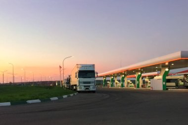 Car fueling station at dawn or in evening during sunset, truck in parking lot. Always open service 24 hours, everyday things. Empty copy space for text.