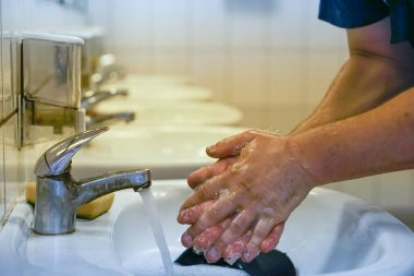 the mechanic washes his dirty hands after a working day a