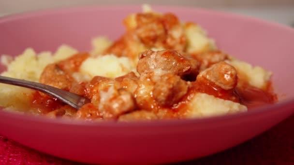 Hovězí guláš s bramborovou kaší, výběrové zaměření, člověk, který jí jídlo vidličkou