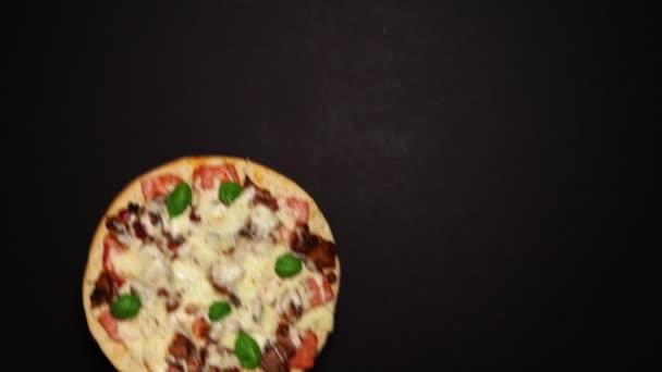 pizza s houbami, šunkou a bazalkou na černém pozadí. Rozumím. Pohled shora. plochý ležel