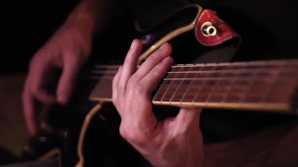 kytarista hraje. Hraj na kytaru. Hipster muž sedí v hospodě. Živá hudba. Kytary a struny.