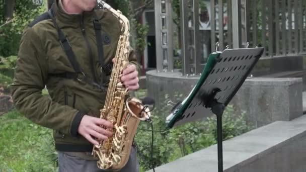egy utcai zenész, egy zöld kabát és szürke nadrág kesztyű nélkül játszik a réz szaxofon az utcán, akkor nem látja a fejét