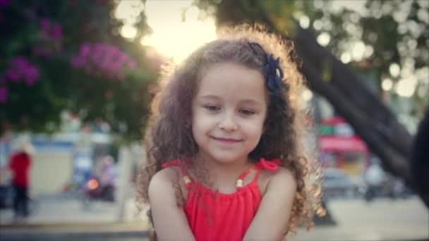 Detail portrétu šťastný roztomilé holčičky s kudrnatými vlasy v červených šatech, sedí v parku a na západ slunce pozadí se dívá na kameru. Stopáže