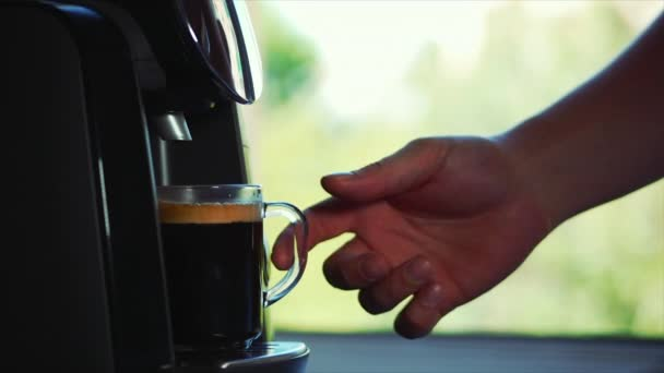 Coffee flows from cofee machine in home. Stock footage.