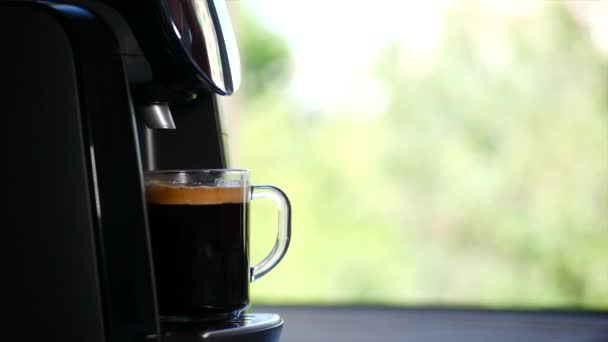 Mans hand takes a mug with a foca. Coffee streams from the coffee machine at home. Stock footage.