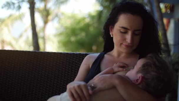 Mutter mit einem Kind im Freien, stillen, ihn beruhigen von Kleinkind Kind Muttermilch geben