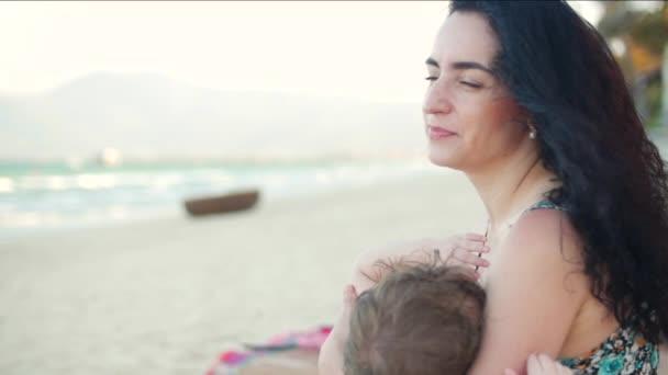 Maminka s dítětem se těší čerstvý vzduch ohřát u moře, Maminka je kojení dítě a lulling mu