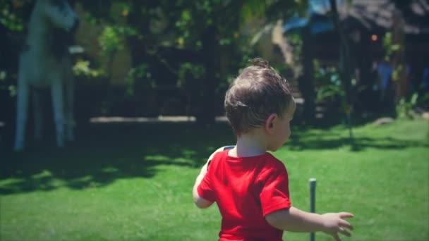 Milý chlapeček hraje s fotbalovým míčem. Stopáže.