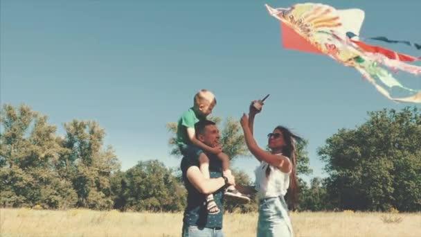 Šťastná rodina, Maminka, Tatínek a syn jsou procházky v přírodě, spouštění had vzduchu. Stopáže.
