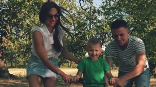 Šťastná rodina, matka, otec a syn jsou procházky přírodou, dítě je jízda na kole, jeho rodiče mu k urychlení pomoci. Šťastní rodiče a dítě se usmívají. Video.