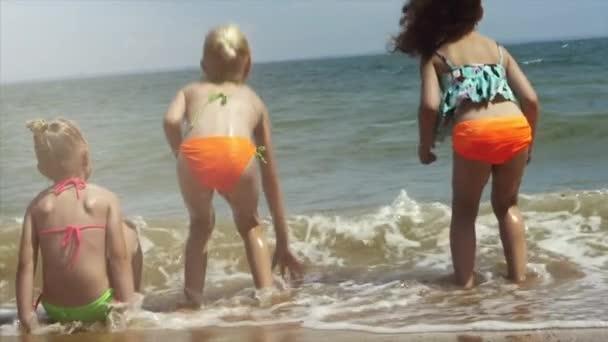 Šťastné děti hrají na pláži při západu slunce. Koncept přátelská rodina.