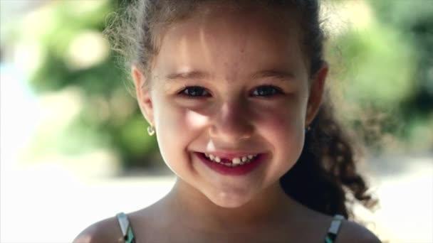 Malé radostné holčičky s kudrnatými vlasy, krásný úsměv a zelené oči při pohledu na fotoaparát, šťastný úsměv.