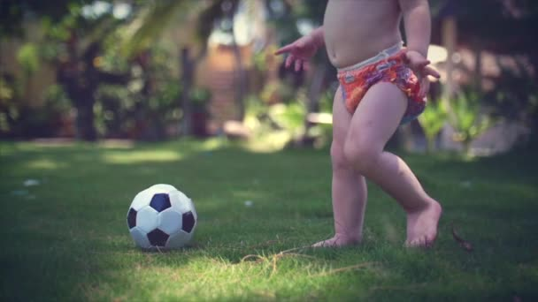 A two-year-old boy likes to play football in the park, run and kick the ball.