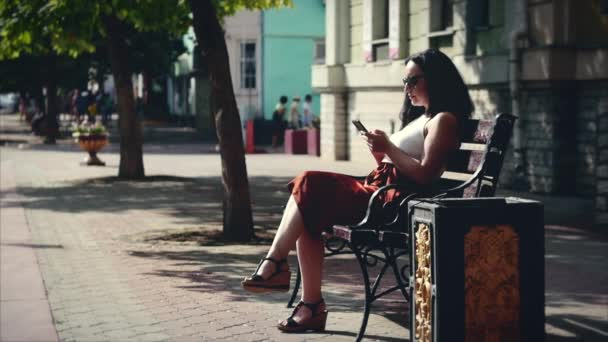 Beautiful business woman of a Caucasian appearance using smart phone technology app sitting on a bench city streets living urban happy lifestyle