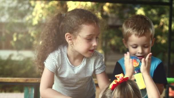 Tři děti v parku hrát pod širým nebem s bublinkami