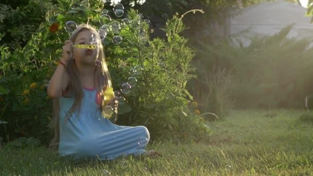 Pomalý pohyb šťastný kavkazské holčičky Fouknout mýdlové bubliny za slunečného dne. Koncept šťastné dětství nebo dětské hry v přírodě