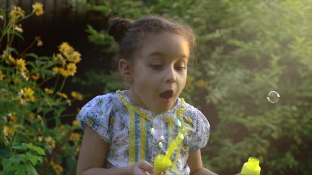 Pomalý pohyb šťastný kavkazské holčičky Fouknout mýdlové bubliny za slunečného dne. Koncept šťastné dětství nebo dětské hry v přírodě.