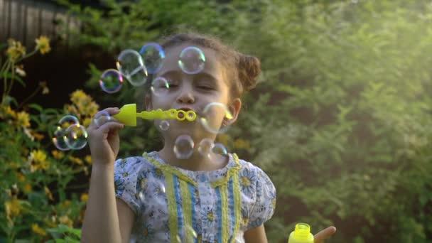 Šťastné dítě fouká mýdlové bubliny v parku. Zpomalený pohyb. Stopáže.