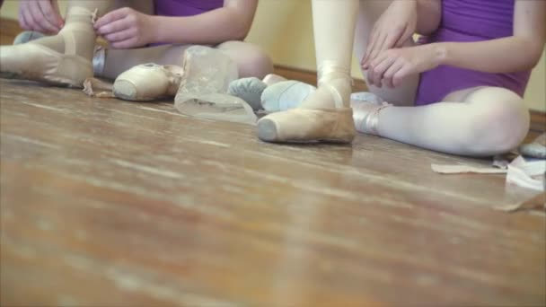 Ballet. Ballet dancer tying slippers around her ankle woman ballerina pointe. 4K.