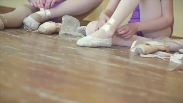 Ballet. Ballet dancer tying slippers around her ankle woman ballerina pointe. 4K.