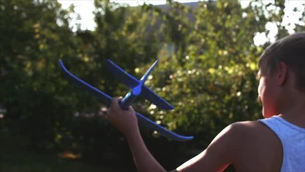 Šťastné dítě hraje s letadlo v rukou běžící na pozadí slunce.