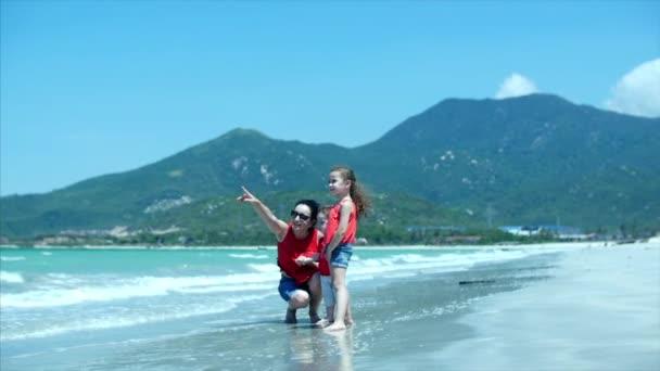 Camping, una giovane famiglia, madre e bambini sono a piedi lungo la riva del mare in riva al mare, madre sta mostrando la sua mano fino al cielo, dicendo qualcosa per i bambini