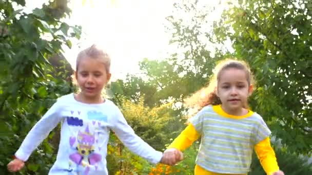 Two happy pretty little girls holding hands and playing in the fresh air