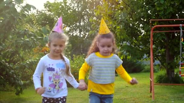 Dvě hezká malá dívky drželi se za ruce a hraje na čerstvém vzduchu.