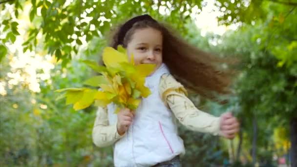 Schöne modische glücklich lächelnd stilvolle freudige Europäische kleine süße Mädchen in einem weißen Jacke Weste und lange Blonde lockige Haare Spaziergänge im Herbst Park genießt glücklich spielen mit Herbst Blätter, laufen