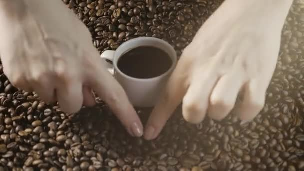 Šálek kávy a kávových zrn. Dámské ruce nakreslit srdce kávová zrna. Bílý šálek kouřící kávy s restovanými fazolkami kolem něj.